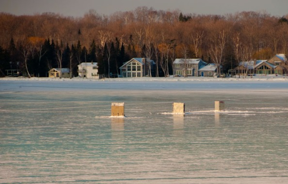 Fish shanties and cottages contemplate each other across Torch Lake
